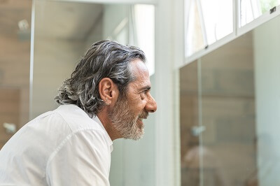 Older man looking at himself in the mirror
