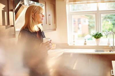 Woman standing in kitchen drinking coffee, looking contemplative