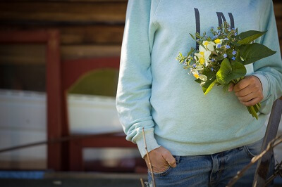 Person holding a bouquet of flowers, including daffodils