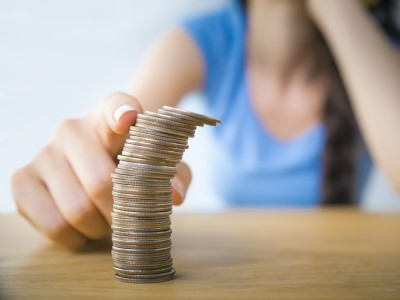 A finger topples a stack of coins.