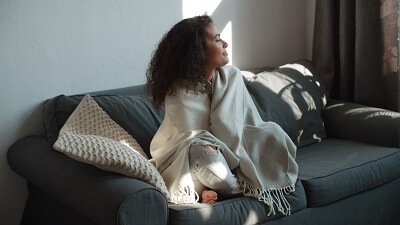 Woman sitting under a blanket at home, relaxing