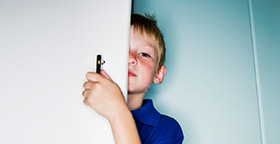 Boy peeking around door