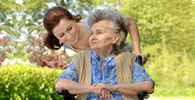 Caregiver with old woman in wheelchair