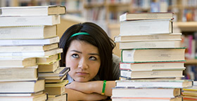 Student surrounded by piles of books