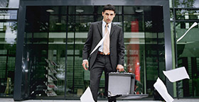 Man with papers falling out briefcase