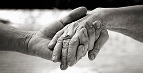 Close up of old couple holding hands