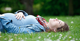 Pregnant woman lying in grass