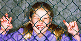 Angry girl behind chain link fence