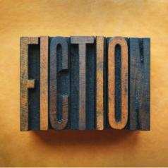 "A wood cut-out of an ink stamp reads ""fiction."""