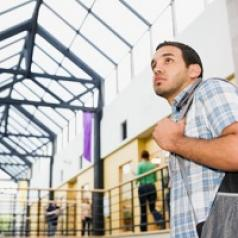 Nervous-looking young man with short dark hair, wearing plaid shirt and backpack. He is standing in a glass-ceilinged college building with many people walking behind him.