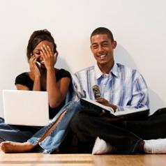 Happy couple with laptop and book