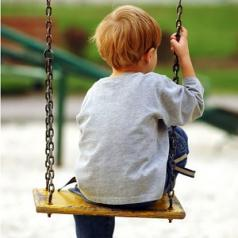 A boy sits on a swing, alone and sad.