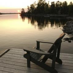 An empty wooded chair sits on a wooden dock as the sun sets over a lake.