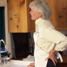 A woman stands at kitchen sink in obvious back pain.
