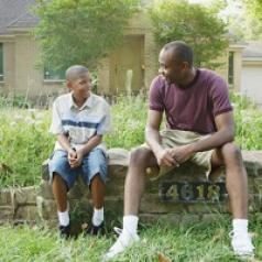A man and his son sit together outside of a house.