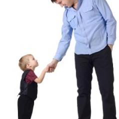 Blonde toddler boy shaking hands with dark-haired middle-aged man