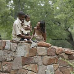 On a stone bridge, young parents admire their child.