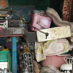 Many broken and useless items are cluttered together, piled up along a wall.