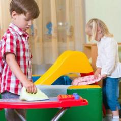 A boy plays with a toy ironing board and a girl plays with folding clothes.