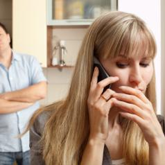 A woman conceals her phone call from her spouse