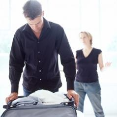 Man packing suitcase while woman talks in background