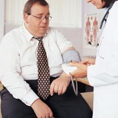 Overweight man having his blood pressure taken by a nurse
