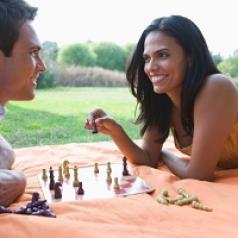Couple playing chess outside