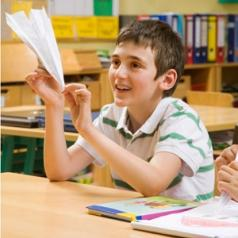 young boy in class with paper airplane