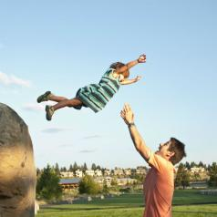 child jumping into arms of dad