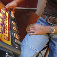 Mid section view of a man playing on a slot machine in a casino