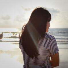Girl stood looking towards the distant sea