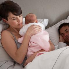 Mother cuddles a newborn baby in bed while the father sleeps