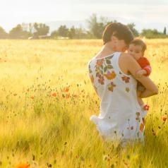Mother holds a baby in a field of poppies