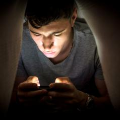 Teenage boy hiding while using a mobile phone