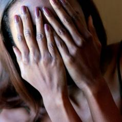 Woman with hands covering face
