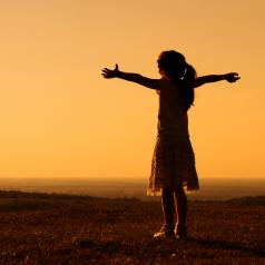 Girl standing outside with her arms outstretched