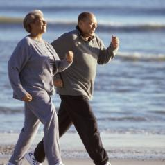 Two seniors walking on the beach together