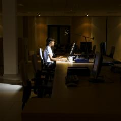 Woman working late in dark office