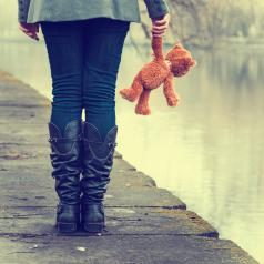 Girl holds teddy bear next to lake