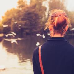 Rear view of red-haired person in black coat watching birds at a lake