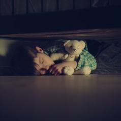 A scared child has fallen asleep under a bed with a teddy bear
