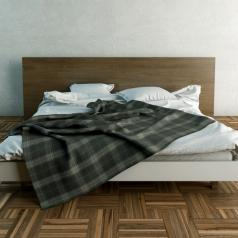 An empty, unmade bed with a plaid blanket in the middle of a room