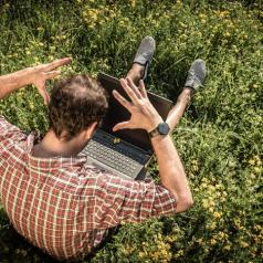 Sitting in grass, laptop in lap, hands on head in frustration