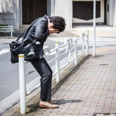 A young professional hides face in hands while leaning against a fence