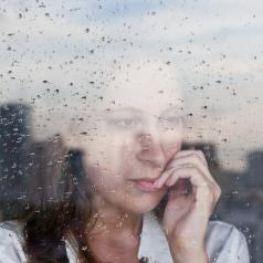Sad woman looking out rainy window at city