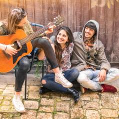 Teens playing music together outside