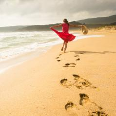 Rear view of person in red dress dancing in carefree way on the beach