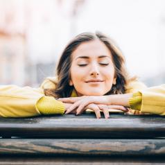 Smiling woman leaning on bench