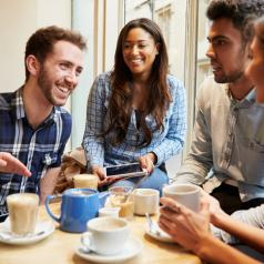 Five young people sit at table in coffee shop. One has digital device open. All are laughing and talking and looking at each other