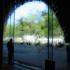 One blurred figure stands against wall of water on a glass window provides an interesting view of the world outside.